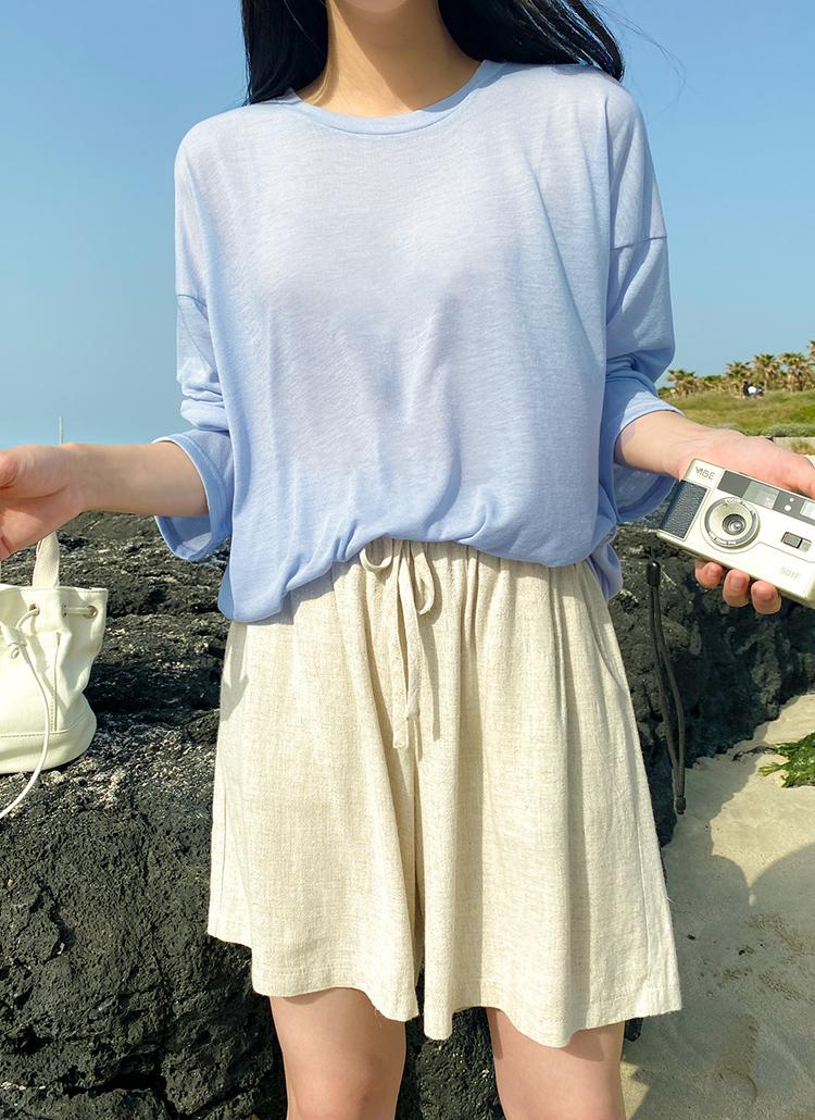 青いドロップショルダーロンTを着た女性