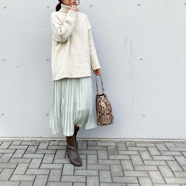 白ニットにシフォンプリーツスカートとブーツを合わせたコーデ