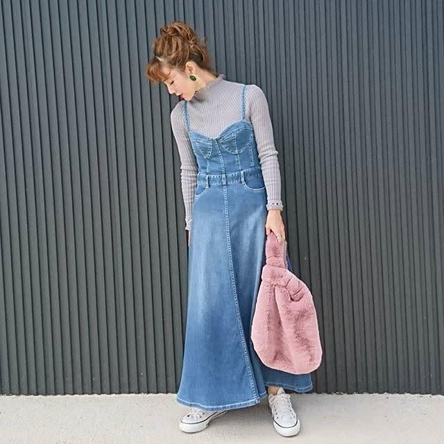 リブニットとジャンバースカートを着用した女性
