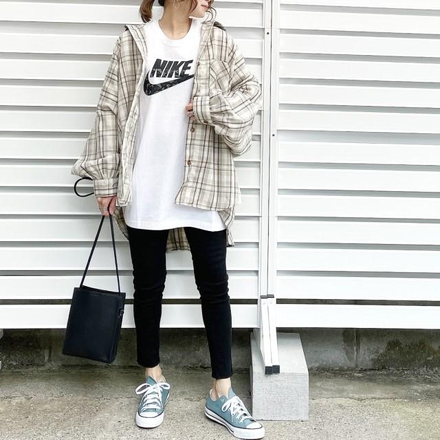 チェックシャツとNIKEのTシャツとスキニーパンツを着用した女性
