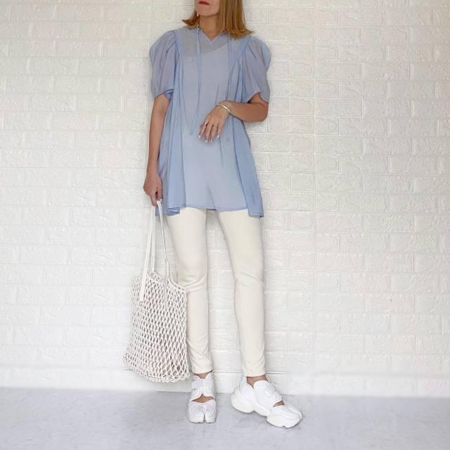 水色シアーブラウスと白パンツと白編みバッグのコーデ