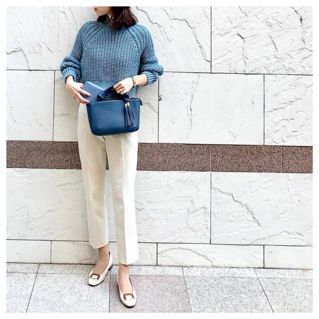 ブルーのニットと白パンツを着用した女性