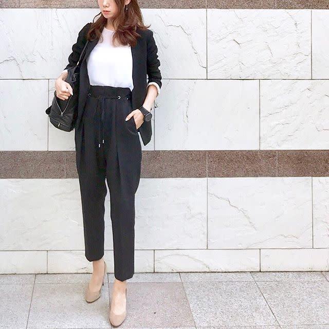 ブラックテーラードジャケットにホワイトトップス、UNITED TOKYOのブラックスラックス、ベージュパンプスの女性
