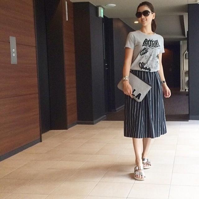 ユニクロユーのグレーTシャツに黒プリーツスカートとシルバーサンダルを合わせたコーデ