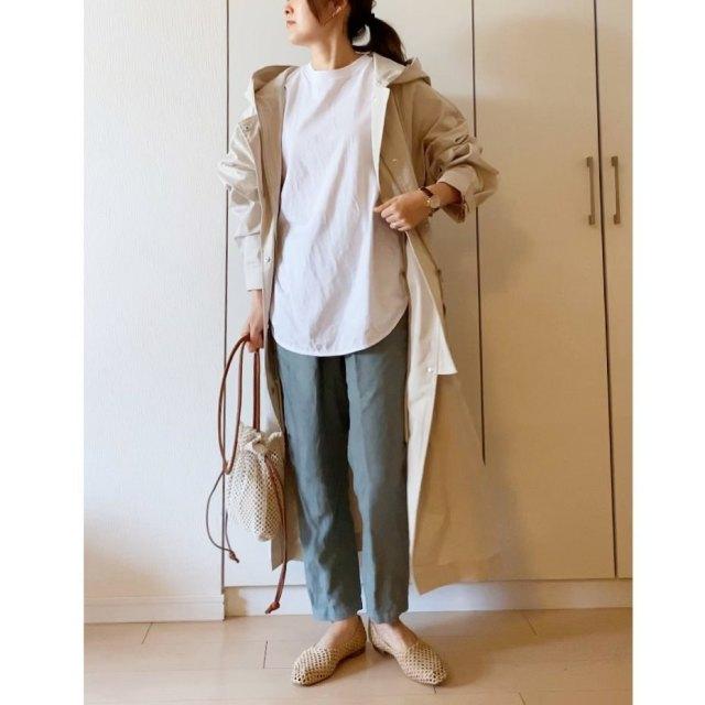 スプリングコートにホワイトTシャツ、FRAMe WORKのグリーンスラックス、ベージュメッシュシューズの女性