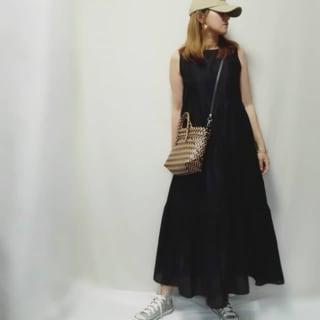 ブラックのワンピースとキャップを着用した女性