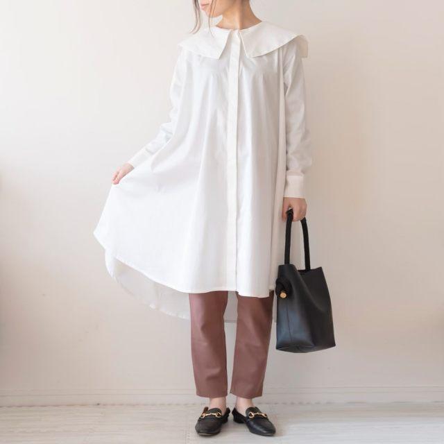 白のロングブラウスとパンツを着用した女性