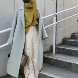 ミントカラーのコートに緑ニットと白パンツを合わせている女性