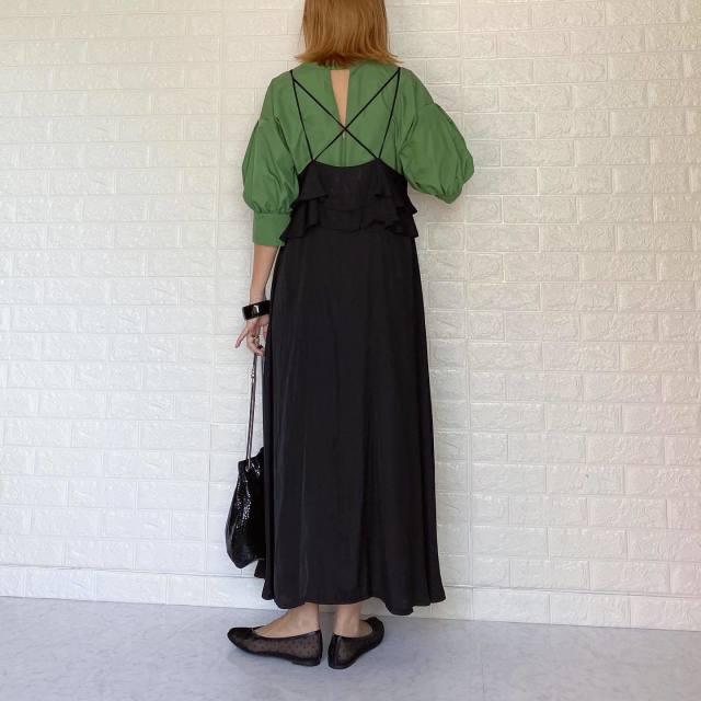 GUのチャイナフラットシューズにブラックのキャミソールワンピースとグリーンブラウスを着ている女性の写真