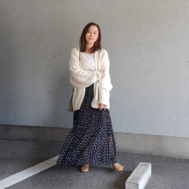 カーディガンとドット柄スカートを着用した女性