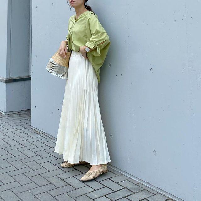 グリーンシャツに白プリーツスカートとパンプスを合わせたコーデ