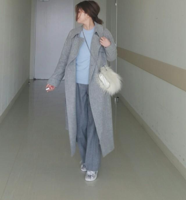 ライトブルーのニットにグレーのコートとグレーのワイドパンツを合わせたコーデ