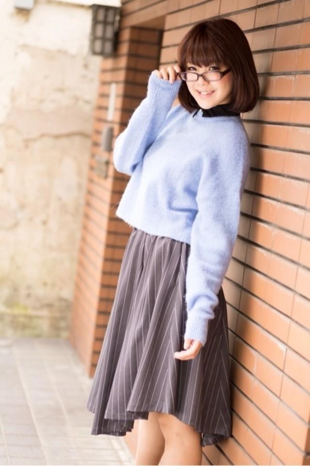 襟付きのライトブルーニットとグレーのスカートを着ている女性
