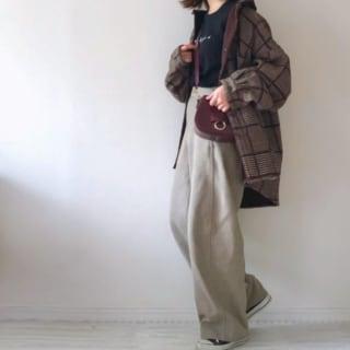 ブラウンのチェックシャツジャケットにハイウエストワイドパンツを履いた女性