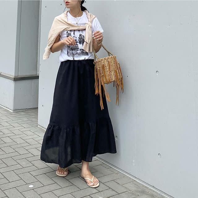 黒のロングスカートのコーデに白プリントTシャツを合わせている女性