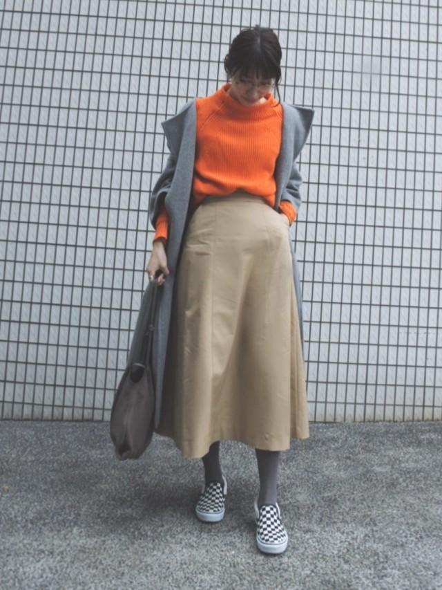 オレンジニットにベージュスカートの女性