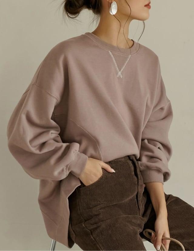 ブラウンのスウェットにコーデュロイのパンツを着ている女性の写真
