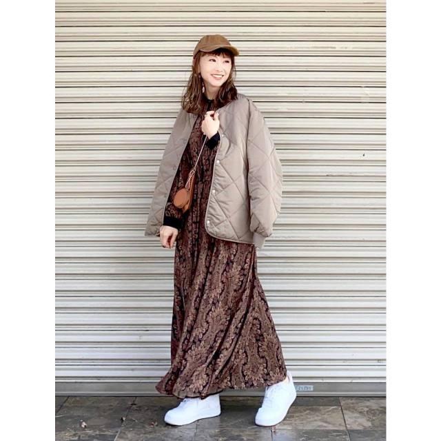 ブラウンのワンピースにキルティングのブルゾンを着ている女性の写真