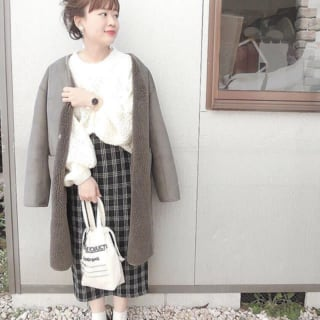 ムートンコートにロングタイトスカートを着ている女性の写真