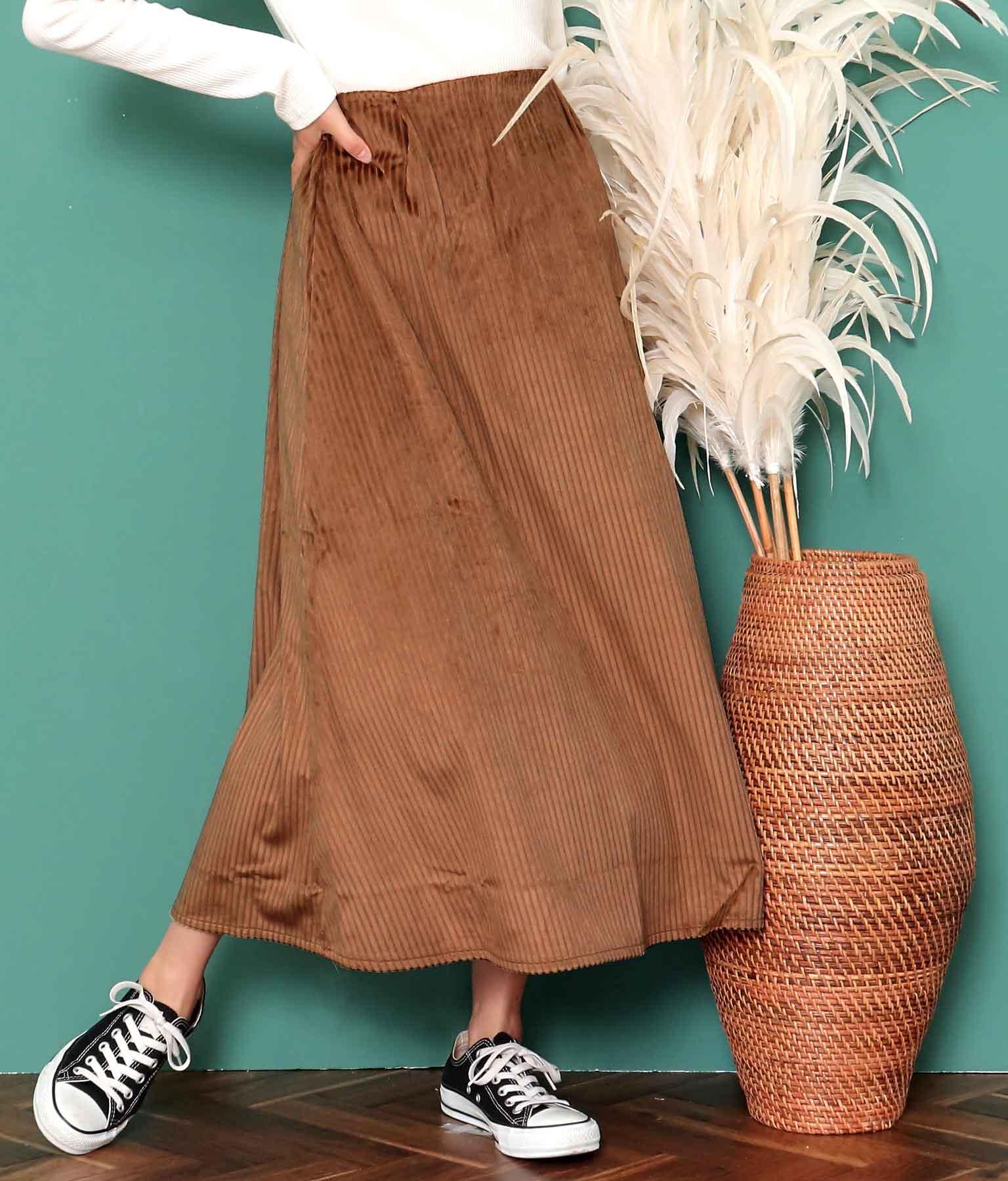 茶色フレアロングスカートに黒スニーカーを合わせている女性