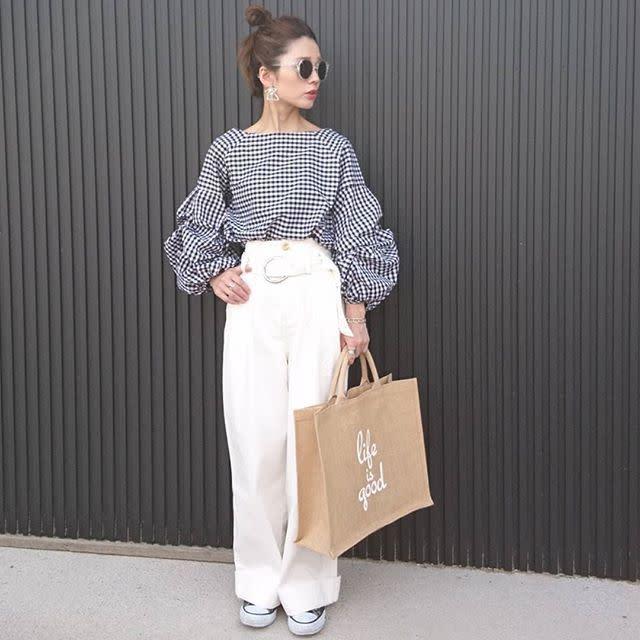 白のワイドパンツにギンガムチェックのブラウスを着た女性