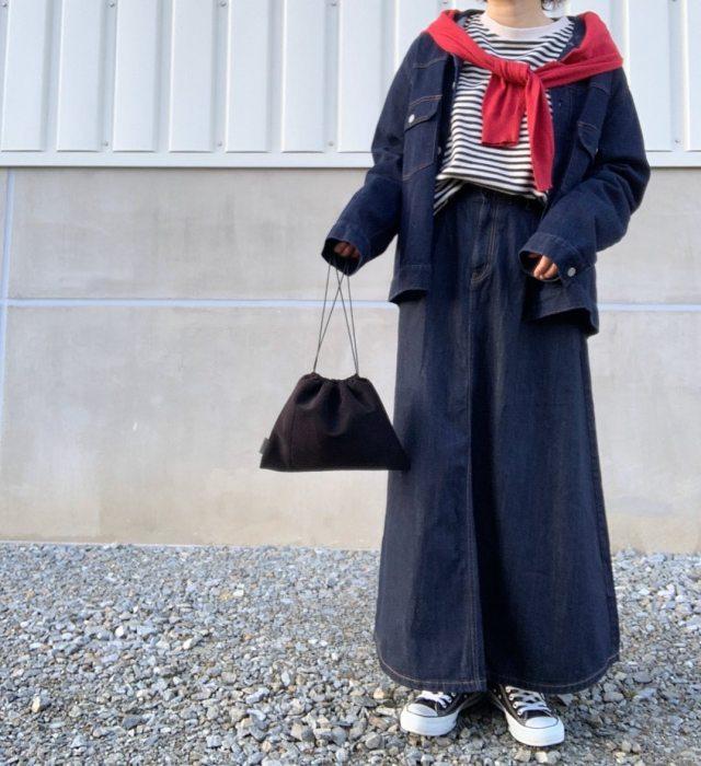 ロングデニムスカートにデニムジャケットのコーデに赤いカーディガンを合わせている女性