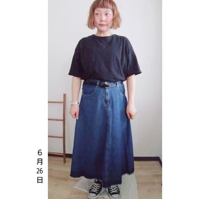 黒のTシャツにデニムロングスカートを合わせている女性