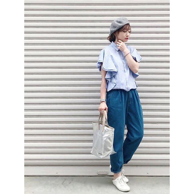水色の変形トップスにインディゴのデニムパンツ、白のスニーカーを合わせた女性