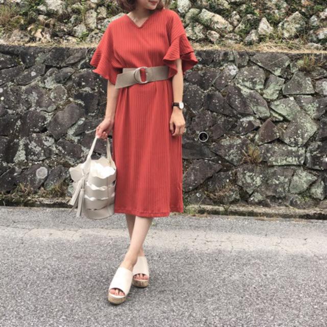 赤袖フリルワンピースにベルトでウエストマークした女性