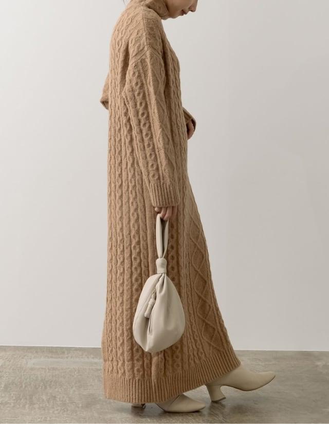 ロング丈のキャメルニットワンピースを着た女性