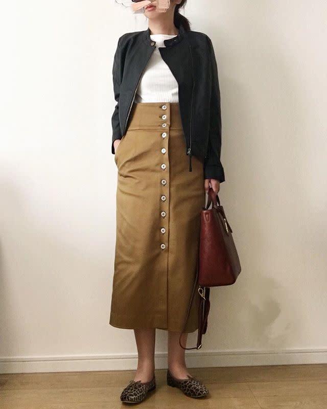 黒のフェイクレザーライダースジャケットにベージュのフロントボタンスカートを合わせたコーデ