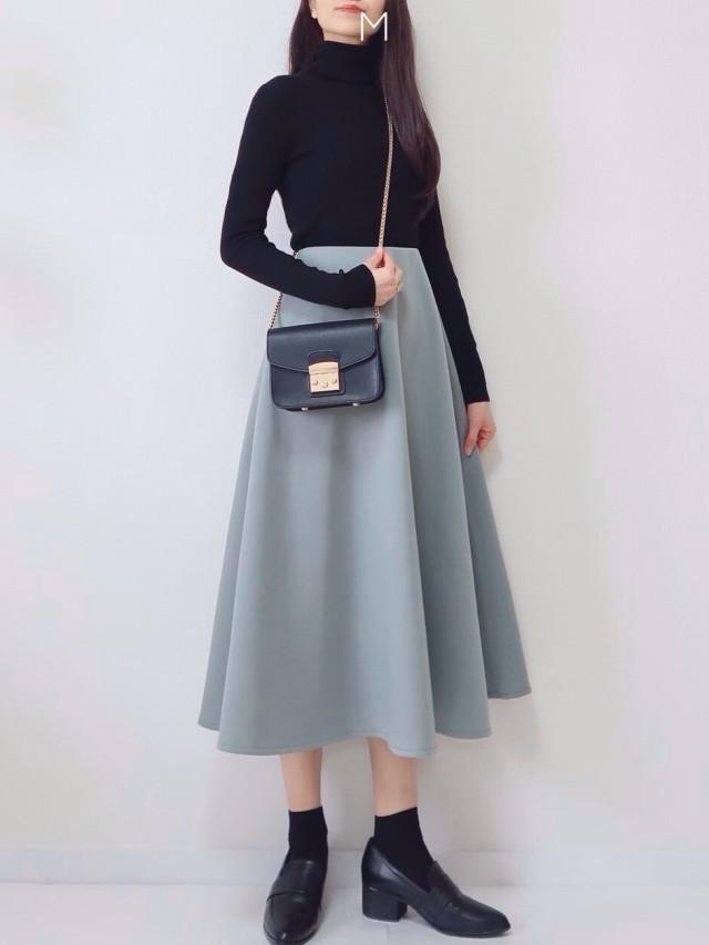 黒タートルニットにミントのスカートのコーデにヒールローファーを合わせている女性