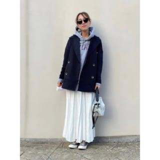 ショートコートとパーカーとスカートを着用した女性
