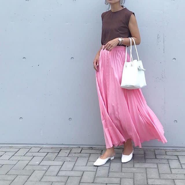タンクトップとプリーツスカートを着用した女性