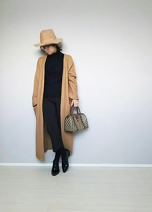 黒のトップスパンツにベージュのコートのコーデにオックスフォードシューズを合わせている女性