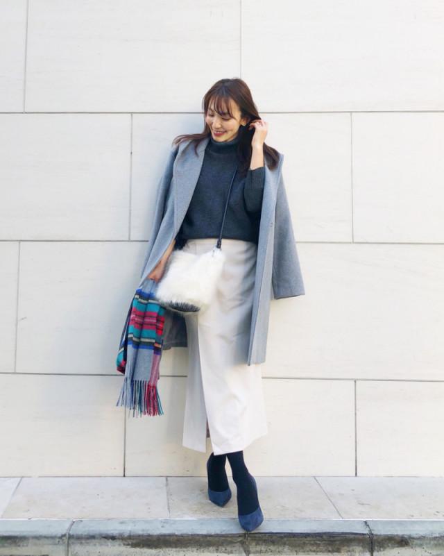 グレーのチェスターコートと白のタイトスカートを着てチェックのストールを持っている女性