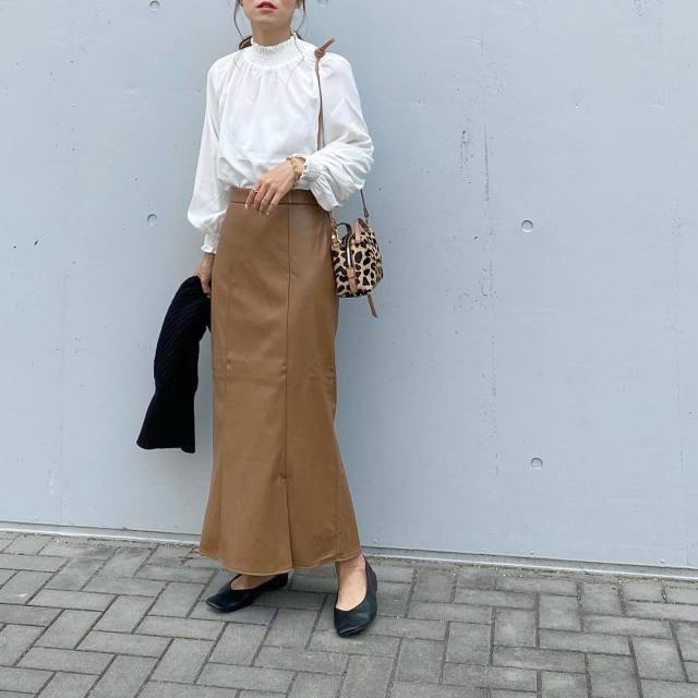 白ブラウスにキャメルのスカートをはいている女性
