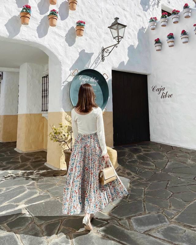 白のカットソーに花柄スカートをはいている女性