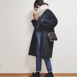 黒のノーカラーコートにベージュのスヌードとパンツを合わせたコーデ