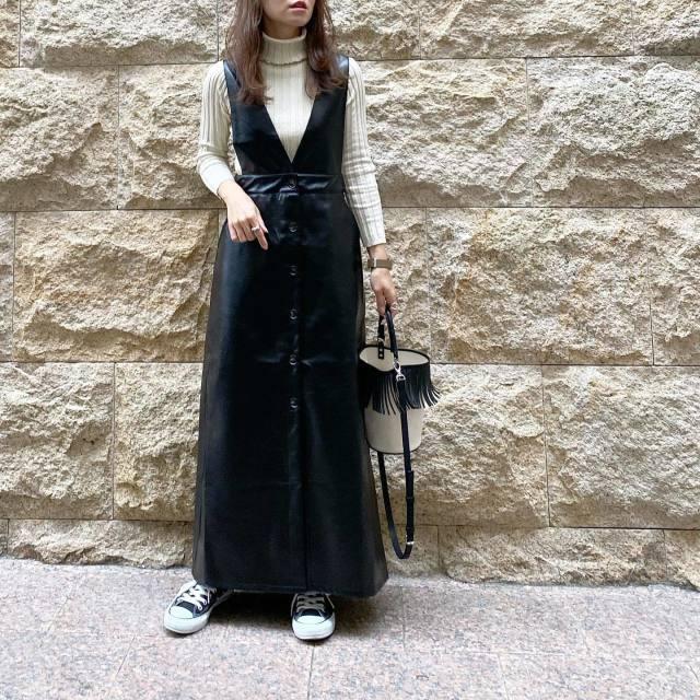 エコレザーのジャンバースカートを着用した女性