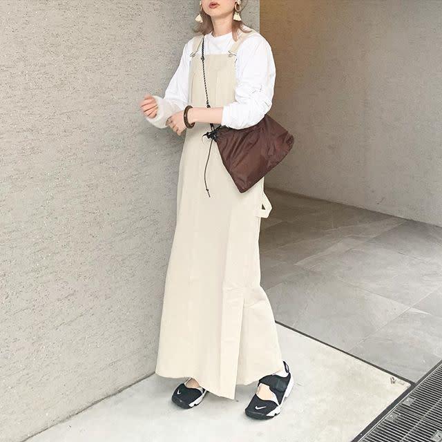 ロンTとジャンバースカートを着用した女性