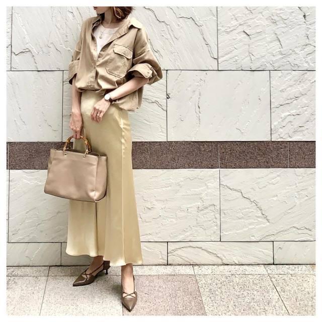 ベージュのミリタリーシャツにベージュのサテンロングスカートを合わせたコーデ