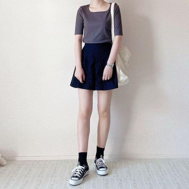 黒Aラインミニスカートにグレーのリブスクエアネックトップスを着た女性