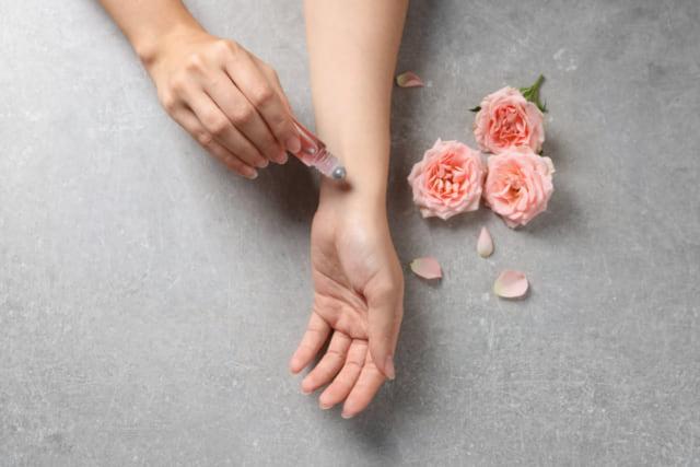 手にバラの香りの香水をつける女性